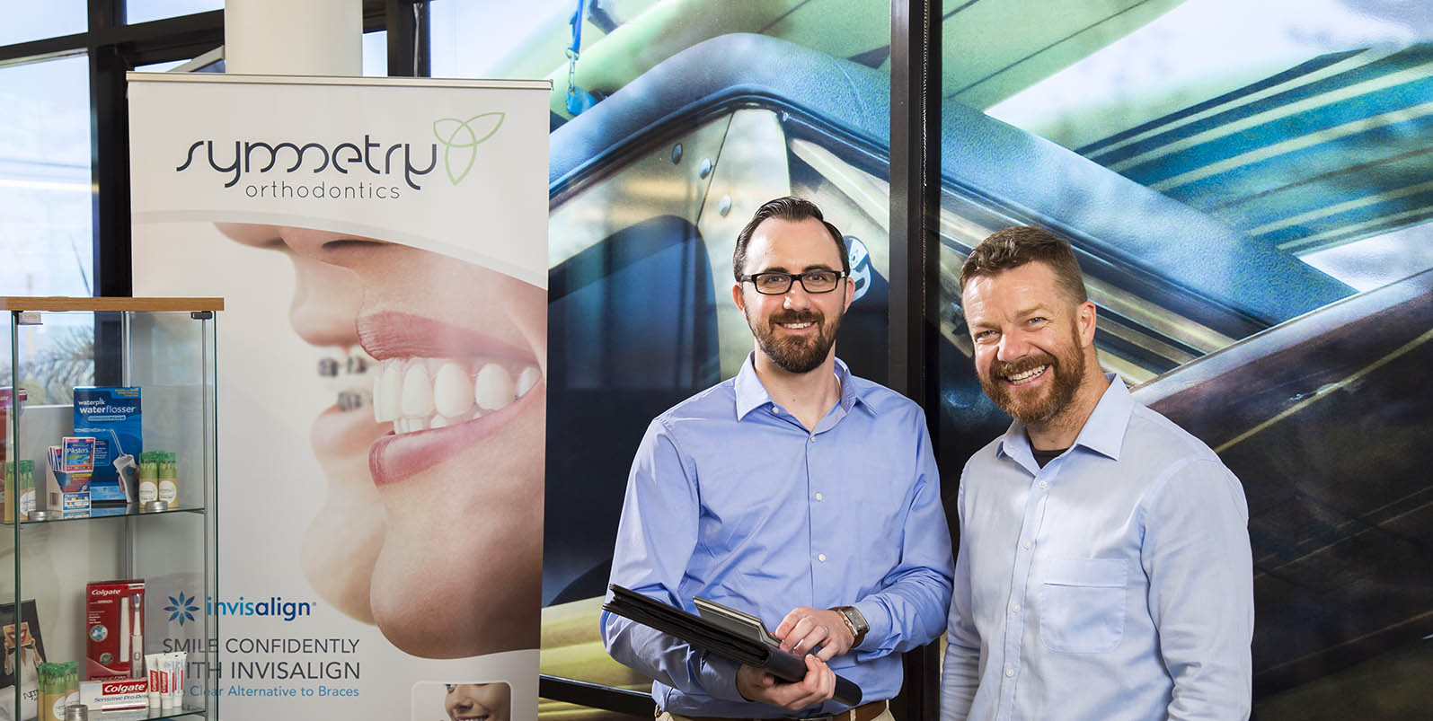 Accountant Jeremy Higgins with Jamie Galbraith standing in front of Symmetry Orthodontics banner